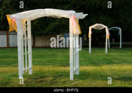 Three white arbors arranged in a yard, in the late sunlight - Stock Photo