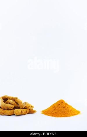 Dried Turmeric rhizomes and turmeric powder on a white background - Stock Photo