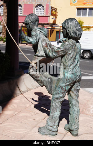 Bronze sculpture in Spain of children playing on swing