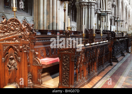 Beautifully formed Choir Stalls with the huge columns in the background catch the eye in Lichfield Cathedral. - Stock Photo