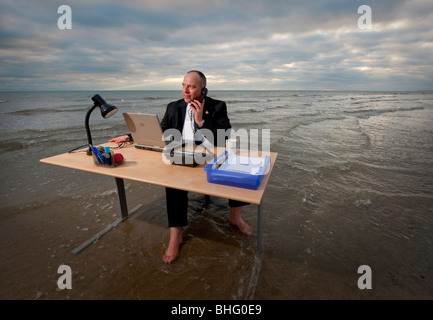 An office with a sea view: Uniglobe Preferred Travel employee braving the elements on Brighton beach, UK.Picture - Stock Photo