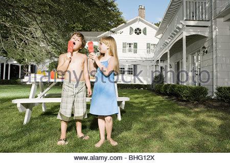 Children eating ice lollies in garden - Stock Photo