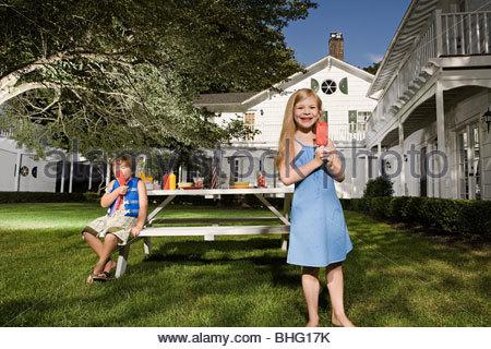 Children eatinbg ice lollies in garden - Stock Photo