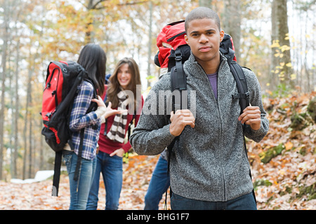 Young people hiking through forest - Stock Photo