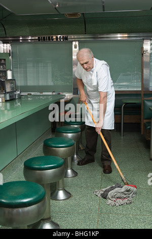 Old cleaner mopping a diner floor - Stock Photo