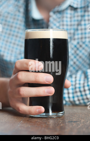 Young man holding pint glass, close up - Stock Photo