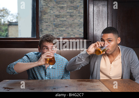 Young men drinking beer in bar
