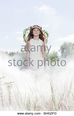 Girl dressed as fairy in cloud of smoke - Stock Photo