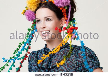 Young woman wearing pom pom headdress - Stock Photo