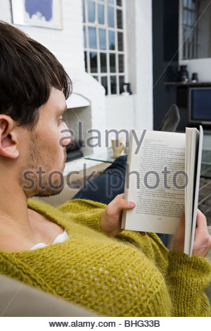 Young man reading book - Stock Photo