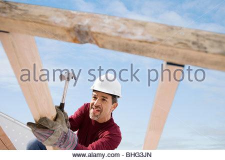 Man using hammer on construction frame - Stock Photo