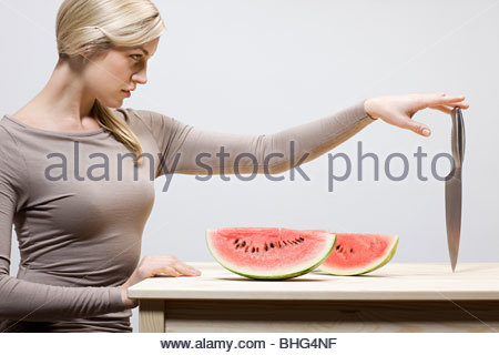 Woman with watermelon slices and knife - Stock Photo