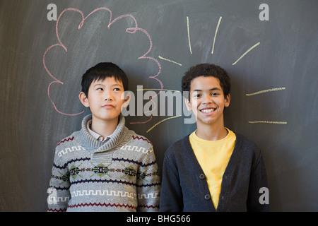 Two boys by a blackboard - Stock Photo