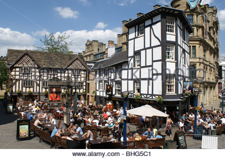 Crowds enjoying a drink in the sunshine outside Sinclairs pub in Shambles Square Manchester city centre - Stock Photo