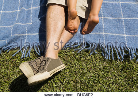 Low section view of man and boy relaxing on picnic blanket - Stock Photo