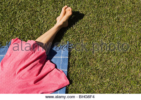 Legs of woman relaxing on picnic blanket - Stock Photo