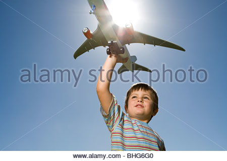 Little boy playing with toy aeroplane - Stock Photo