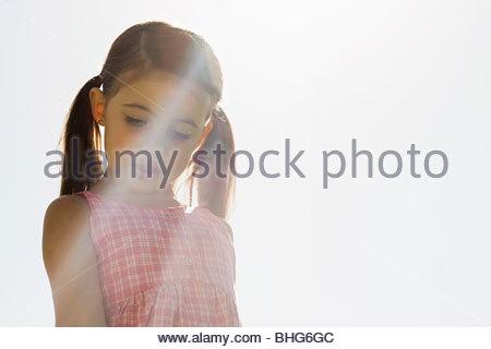 Portrait of little girl standing in sunlight - Stock Photo