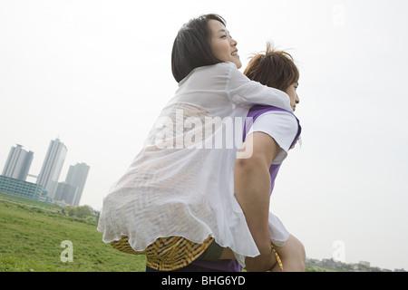Young man giving girlfriend piggyback - Stock Photo