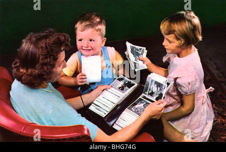 A mother and children looking at photos in a family album, Blackwood, New Jersey, USA, 1956. - Stock Photo