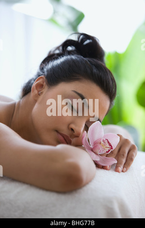 Young woman on massage table with orchid flowers - Stock Photo