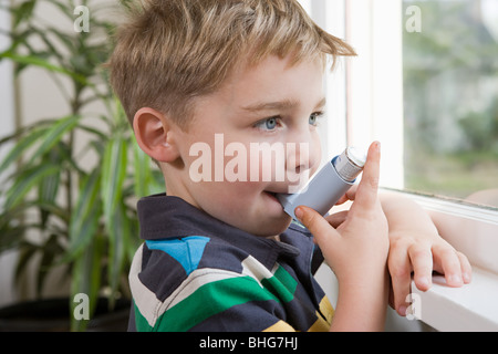 Boy taking asthma inhaler - Stock Photo