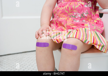 Girl with plasters on her knees - Stock Photo