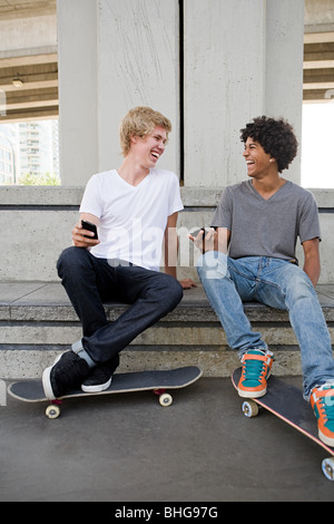 Teenage boys with cellphones and skateboards - Stock Photo