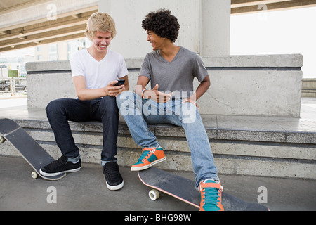 Teenage boys with skateboards and cellphone - Stock Photo