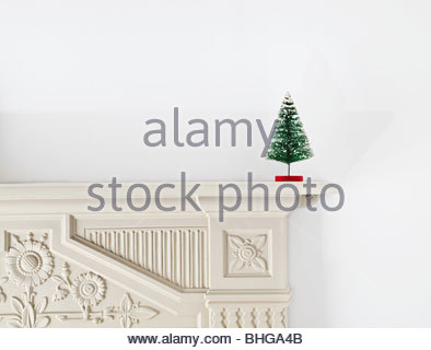 Miniature christmas tree on mantlepiece - Stock Photo