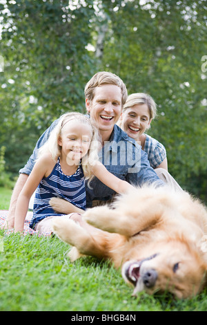 Family in the park with golden retriever - Stock Photo