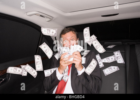 Wealthy businessman in the back of a car - Stock Photo