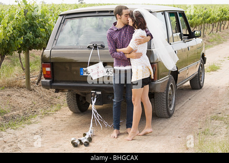 Newlywed couple kissing by vehicle - Stock Photo