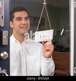 man at door saying 'open' - Stock Photo