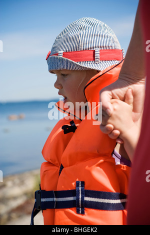 A child wearing a life jacket, Sweden. - Stock Photo