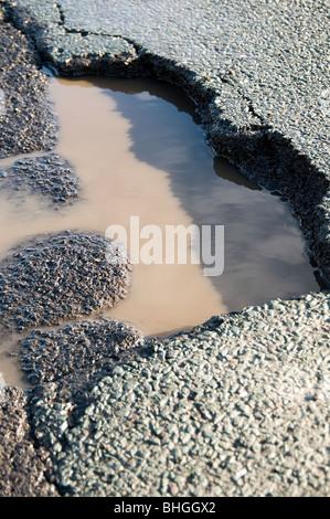 pothole potholes pot hole holes road roads with winter frost damage damaged rut ruts rutted ice heavy - Stock Photo