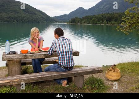 A young couple having a picnic by a lake - Stock Photo
