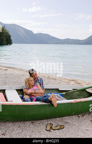 A young couple daydreaming in a boat - Stock Photo