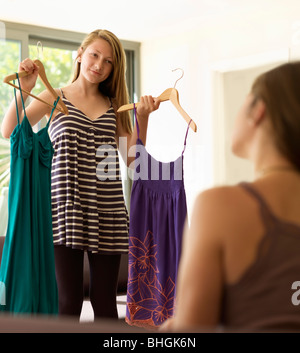 teenage girl showing dresses to mother - Stock Photo