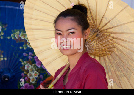 Female painter painting parasol designs, Bor Bo Sang Factory Umbrella Village, Sankampaeng Road, Chiang Mai, Northern - Stock Photo