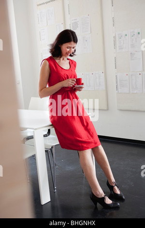 woman in red dress holding red cup - Stock Photo