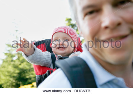 father and baby in backpack hiking - Stock Photo