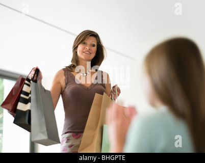 mother showing shopping to teenage girl - Stock Photo