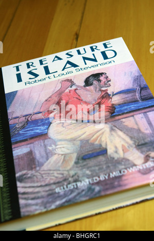 The classic novel Treasure Island lying on a wooden surface - Stock Photo