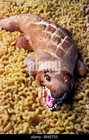 Alligator made of sour dough bread on pasta - Stock Photo