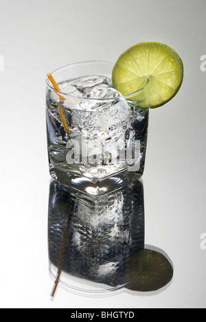 Gin or Vodka and club soda or tonic mixed drink with lime slice garnish on a grey background - Stock Photo