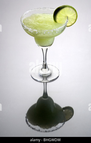 Frozen Margarita mixed drink with lime slice garnish on plain gray background with reflection - Stock Photo