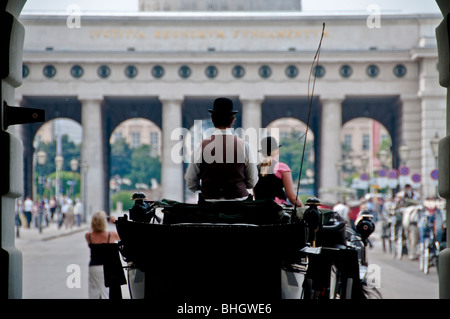 A Viennese Fiaker horse carriage drives through the gates at Hofburg Palace in Vienna Austria - Stock Photo