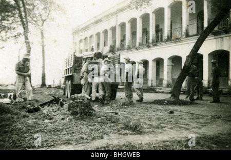 Members of the French Foreign legion unload a truck near a colonial style building. architecture. horizontal black - Stock Photo