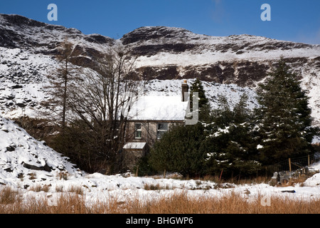 Old snow covered house surrounded by trees near Gloddfa Ganol slate quarry on the crimea on the A470 out of Blaenau - Stock Photo